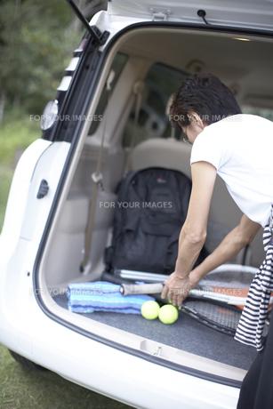 車に積んだテニスラケットを取る女性の素材 [FYI01126655]