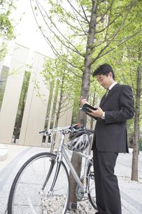 手帳を見るビジネスマンと自転車の素材 [FYI01128995]