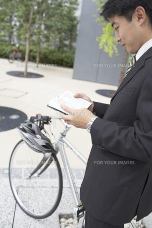手帳を見るビジネスマンと自転車の素材 [FYI01129013]