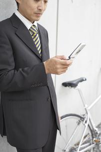 携帯電話を見るビジネスマンと自転車の素材 [FYI01129183]