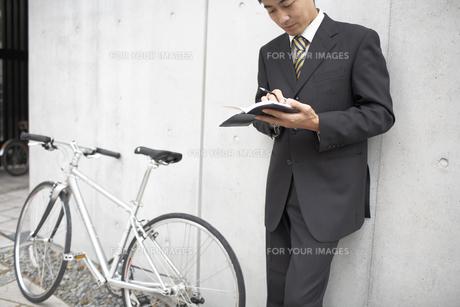 手帳を見るビジネスマンと自転車の素材 [FYI01129188]