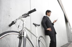 携帯電話を見るビジネスマンと自転車の素材 [FYI01129195]
