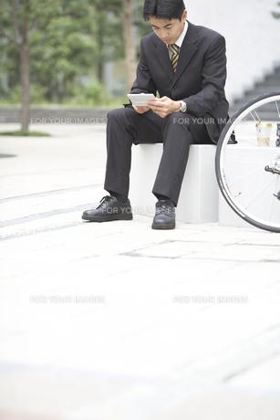システム手帳を見るビジネスマンと自転車の素材 [FYI01129241]
