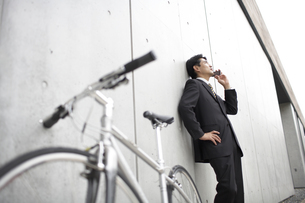 携帯電話で話すビジネスマンと自転車の素材 [FYI01129258]