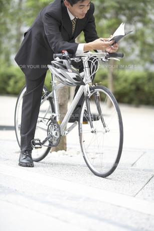 自転車に乗り手帳を見るビジネスマンの素材 [FYI01129272]