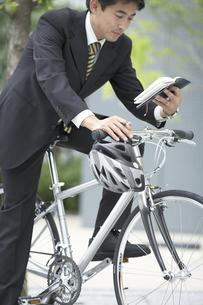 自転車に乗り手帳を見るビジネスマンの素材 [FYI01129277]