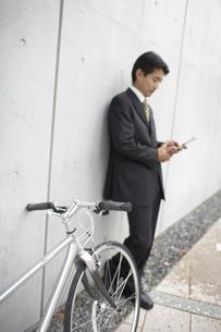 携帯電話を見るビジネスマンと自転車の素材 [FYI01129291]