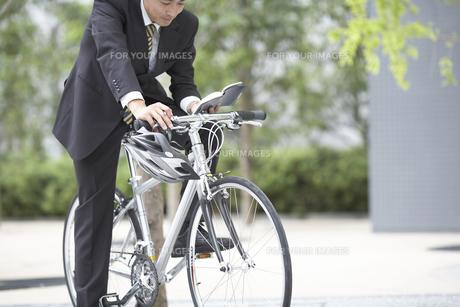 自転車に乗り手帳を見るビジネスマンの素材 [FYI01129296]