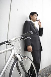 携帯電話で話すビジネスマンと自転車の素材 [FYI01129311]