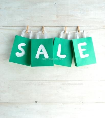 木製ピンチで吊るしたグリーンのショッピングバッグ セール文字入りの写真素材 [FYI01132202]