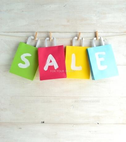 木製ピンチで吊るしたパステルカラー4色のショッピングバッグ セール文字入りの写真素材 [FYI01132204]