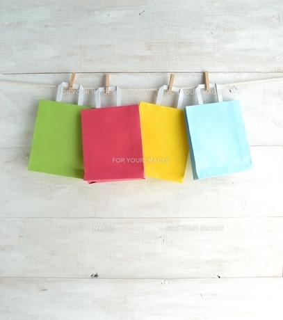 木製ピンチで吊るしたパステルカラー4色のショッピングバッグ の写真素材 [FYI01132207]