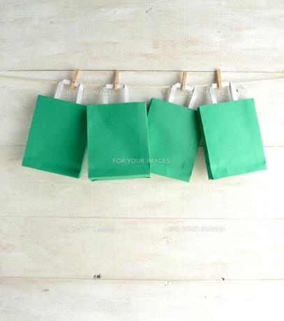 木製ピンチで吊るした緑色のショッピングバッグ の写真素材 [FYI01132209]