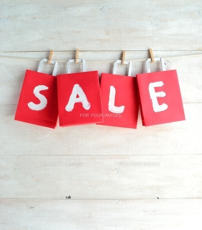 木製ピンチで吊るした赤色のショッピングバッグ セール文字入りの写真素材 [FYI01132211]