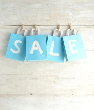 木製ピンチで吊るした水色のショッピングバッグ セール文字入りの写真素材 [FYI01132214]