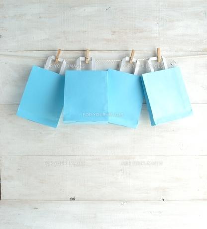 木製ピンチで吊るした水色のショッピングバッグの写真素材 [FYI01132216]