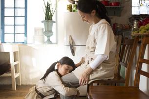 母親の膝の上に顔をのせて甘える女の子の素材 [FYI01136498]