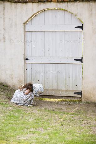 扉の隙間を覗く女の子の素材 [FYI01137857]