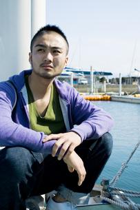 ヨットハーバーの桟橋に座る日本人男性の素材 [FYI01138610]