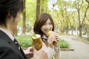 サンドウィッチを食べるビジネスマンとビジネスウーマンの素材 [FYI01139609]