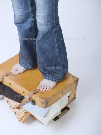 スーツケースから溢れた荷物を押さえる足の素材 [FYI01140233]