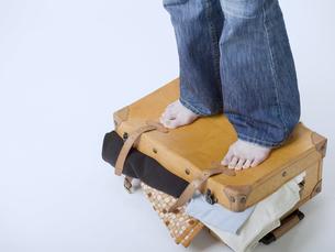 スーツケースから溢れた荷物を押さえる足の素材 [FYI01140326]