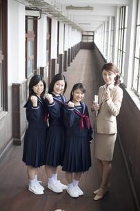 ガッツポーズをする女子中学生3人と先生の素材 [FYI01140864]