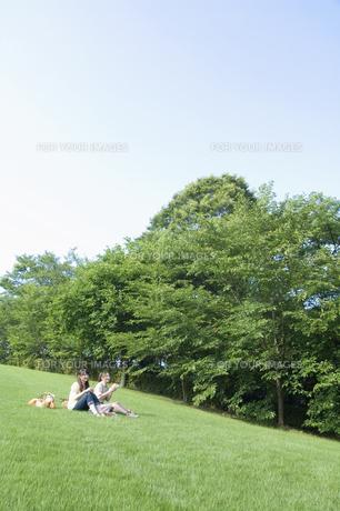 草原でピクニックをする女性2人の素材 [FYI01141643]