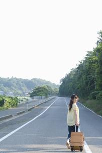 キャリーケースを引き道路を歩く女性の素材 [FYI01141666]