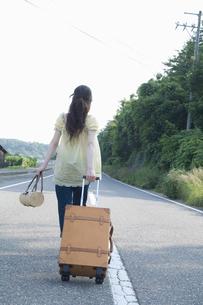 キャリーケースを引き道路を歩く女性の後ろ姿の素材 [FYI01141697]