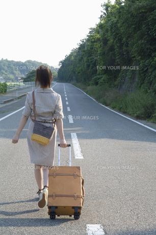 キャリーケースを引き道路を歩く女性の後ろ姿の素材 [FYI01142065]