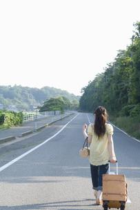 キャリーケースを引き道路を歩く女性の後ろ姿の素材 [FYI01142283]