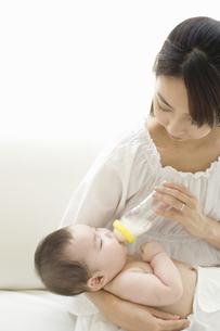お母さんに抱かれてミルクを飲む赤ちゃんの素材 [FYI01142654]