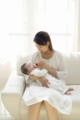 お母さんに抱かれて哺乳瓶でお茶を飲む赤ちゃんの素材 [FYI01142692]