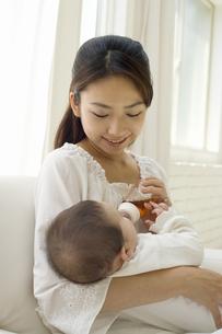 お母さんに抱かれて哺乳瓶でお茶を飲む赤ちゃんの素材 [FYI01142707]