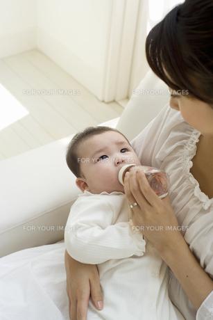 お母さんに抱かれて哺乳瓶でお茶を飲む赤ちゃんの素材 [FYI01142709]