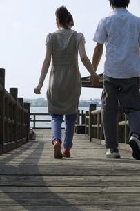 桟橋を歩くカップルの後ろ姿の素材 [FYI01142865]