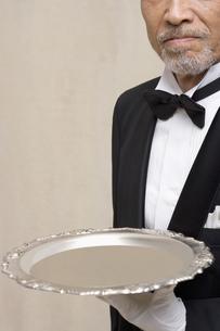 銀のトレイを持つシニア男性の素材 [FYI01142993]