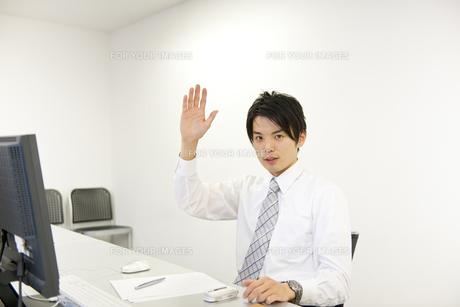 デスクで右手を挙げるビジネスマンの素材 [FYI01143379]
