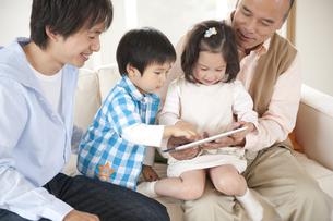 ソファに座る3世代親子の素材 [FYI01143380]