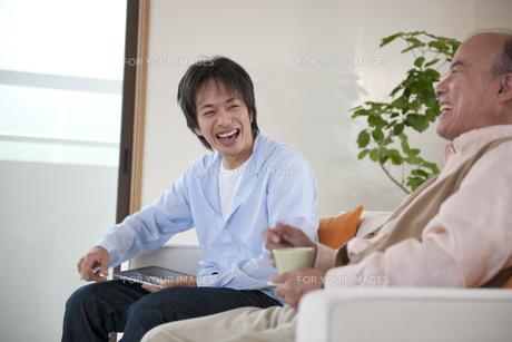 ソファに座る父と息子の素材 [FYI01143385]