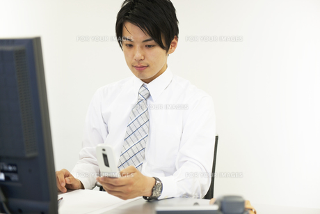 携帯電話をみるビジネスマンの素材 [FYI01143386]