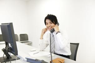 笑顔で電話をかけるビジネスマンの素材 [FYI01143392]