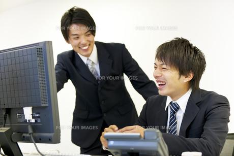 パソコンの画面を見て笑い合うビジネスマン達の素材 [FYI01143406]