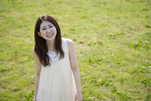 草原に立つ笑顔の女性の素材 [FYI01143494]