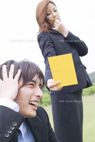 イエローカードを出すビジネスウーマンと頭を抱えたビジネスマンの素材 [FYI01143518]