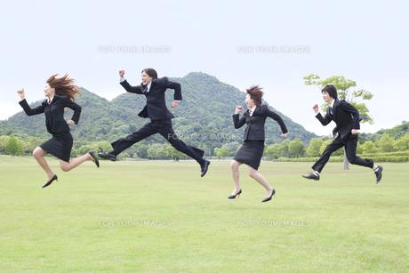 草原でジャンプをするビジネスマンとビジネスウーマンの素材 [FYI01143519]
