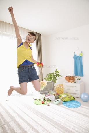 ジャンプをしながら片手を挙げる女性の素材 [FYI01143521]