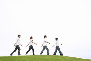 丘の上を一列で歩く若者達の素材 [FYI01143540]