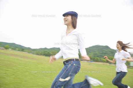 草原を走る女性2人の素材 [FYI01143545]